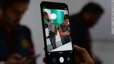 An Indian consumer holds the newly-launched Xiaomi Redmi Note 5 smartphone during a promotional event in New Delhi on February 14, 2018.