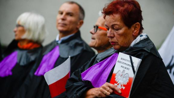 A woman dressed as a Supreme Court judge holds a copy of the Polish constitution during a protest Thursday.