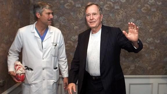 Former President George Bush, center, waves as he leaves with cardiologist Mark Hausknecht, left, and Bush