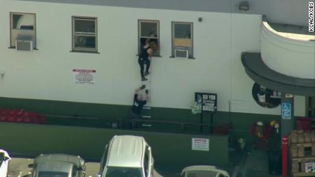 People are crawling out a back window at Trader Joe in Los Angeles.