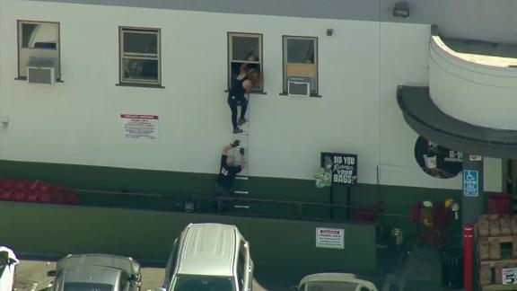 People crawl out of a back window at the Trader Joe's in Los Angeles.