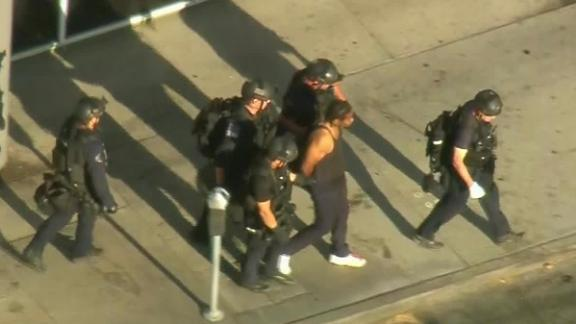 Aerial footage shows police leading the suspect away in handcuffs Saturday after the standoff.