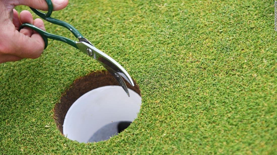 A greenskeeper trims the edges of a hole during the final round of the Open.