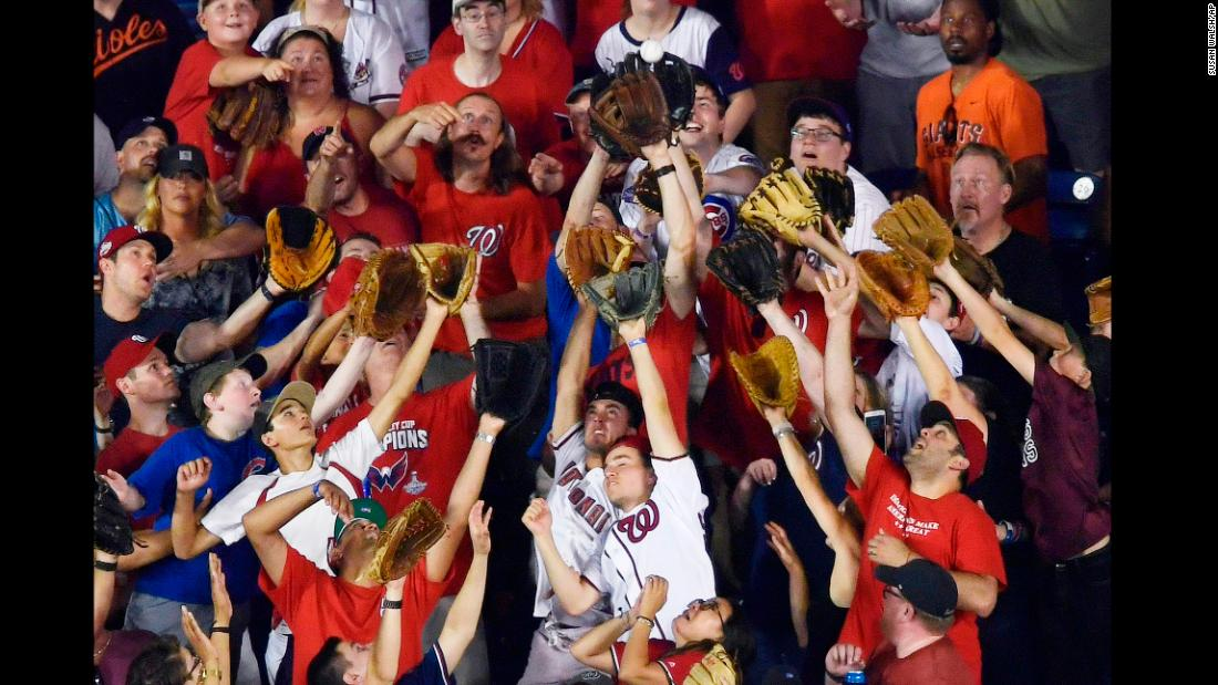 Fans reach for a ball during the Major League Baseball Home Run Derby on Monday, July 16.