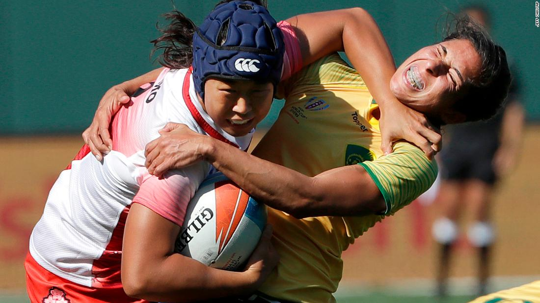 Japan's Noriko Taniguchi, left, breaks a tackle from Brazil's Amanda Araujo during a Rugby World Cup Sevens match on Friday, July 20.