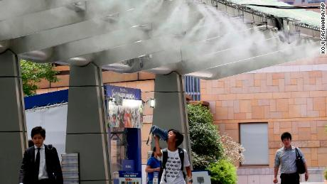 People cool down under the cooling mist spot in Tokyo on July 23.