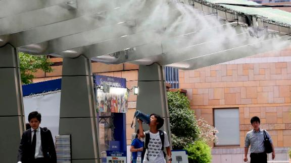 People cool down under the cooling mist spot in Tokyo, Monday, July 23, 2018.