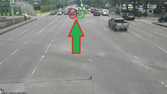 The suspect, circled in red, nears Hausknecht on the road.