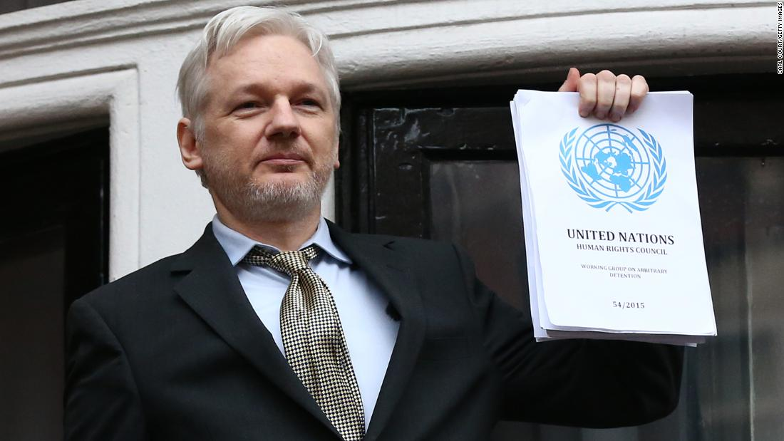 Assange, on the balcony of the Ecuadorian Embassy, holds up a United Nations report in February 2016. The United Nations Working Group on Arbitrary Detention said that Assange was being arbitrarily detained by the governments of Sweden and the United Kingdom.