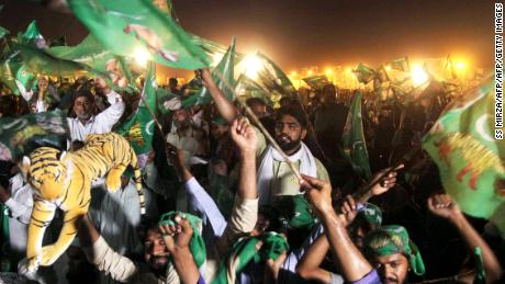Supporters of Shahbaz Sharif, the younger brother of ousted Pakistani Prime Minister Nawaz Sharif and head of Pakistan Muslim League-Nawaz (PML-N), chant slogans and wave flags during a campaign meeting ahead of the general election in Multan on July 22, 2018.