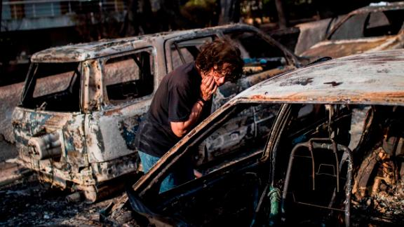 A woman searches for her dog Tuesday after the fire in Mati, near the Greek capital of Athens.