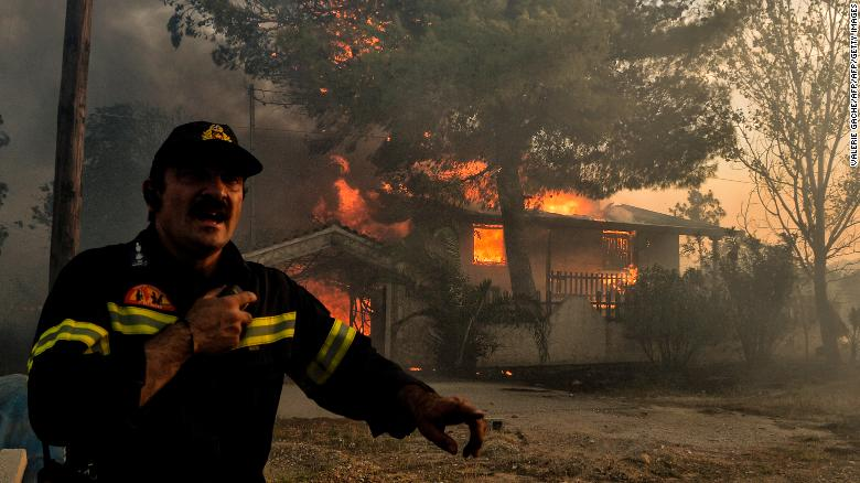 A firefighter reacts as a house burns in Kineta.