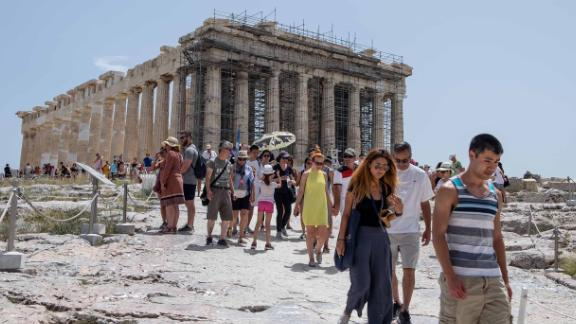 Tourists leave the Acropolis after authorities decided to close the archaeological site as a precaution.