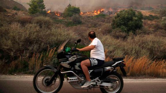 A motorcyclist passes burning brush on a road near Kineta.