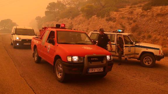 Smoke fills the sky as emergency workers block a road near Kineta.