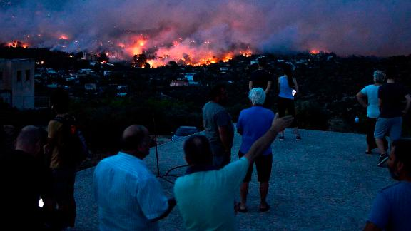 People watch as a wildfire takes hold in the town of Rafina on July 23.
