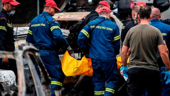 Emergency workers remove a victim's body in Mati on July 24.