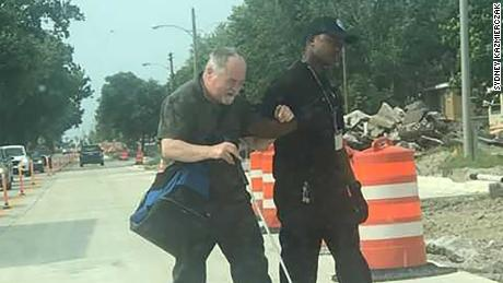 Thaddaus Turner, a public bus driver, walks Gene Hubbard, who is blind, across the road.