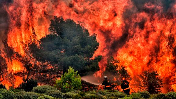 Firefighters try to extinguish flames during a wildfire at the village of Kineta, near Athens, on July 24, 2018. - Raging wildfires killed 74 people including small children in Greece, devouring homes and forests as terrified residents fled to the sea to escape the flames, authorities said Tuesday. (Photo by ANGELOS TZORTZINIS / AFP)        (Photo credit should read ANGELOS TZORTZINIS/AFP/Getty Images)