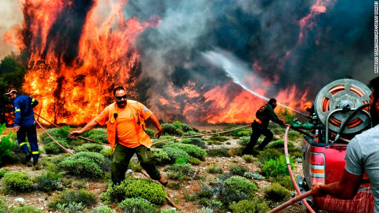 Firefighters and volunteers try to extinguish flames in Kineta, Greece, on Tuesday, July 24.