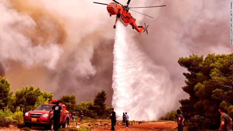 A firefighting helicopter drops water to extinguish flames Tuesday in the village of Kineta.
