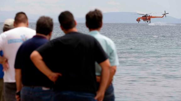People watch as a helicopter collects seawater to fight the wildfires in Mati.
