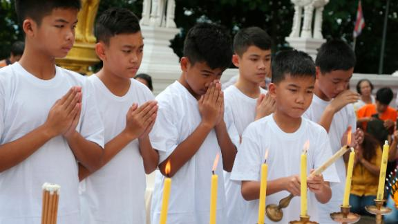 Chanin Vibulrungruang lights a candle with members of the rescued soccer team during a Buddhist ceremony on July 24.