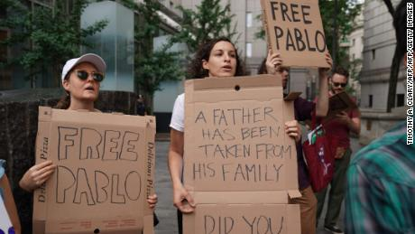 Protesters used pizza box protest signs to demonstrate outside a  New York court Tuesday.
