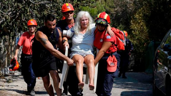 Members of a rescue team carry an injured woman Wednesday in Mati.