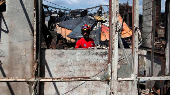 A member of a rescue team searches a burned house Wednesday in Mati.