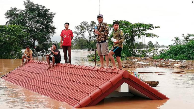 Villagers take refuge from the flood waters on a rooftop in the Attapeu province of Laos on Tuesday, July 24, 2018.