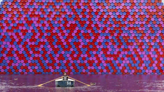 London, UK: As a heatwave hits the UK capital, a woman rows past the London Mastaba, a floating sculpture created by Romanian artist Christo in the Serpentine lake in Hyde Park.