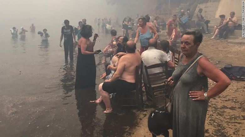 People take refuge Monday from the fires along the beach north of Mati.