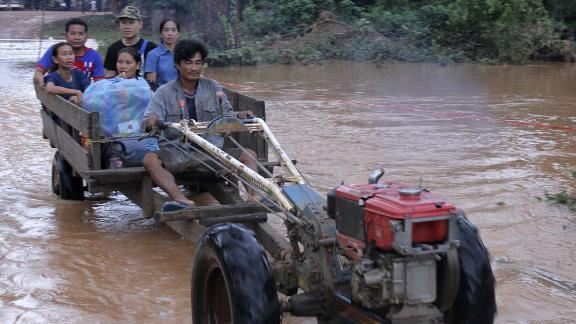 Residents cross flooded areas of Sanamxai, Attapeu province on Wednesday.