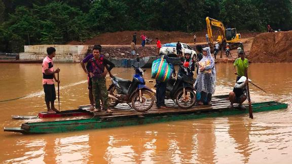 People use a makeshift ferry to cross the swollen Xe Khong river on July 25.