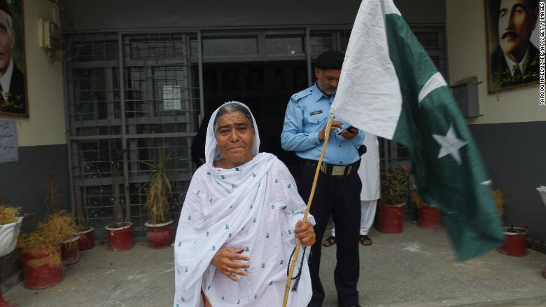 A Pakistani woman walks out of a polling station holding the country's national flag after casting her ballot.