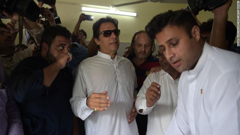 Pakistan's cricketer-turned politician Imran Khan arrives at a polling station to cast his vote.