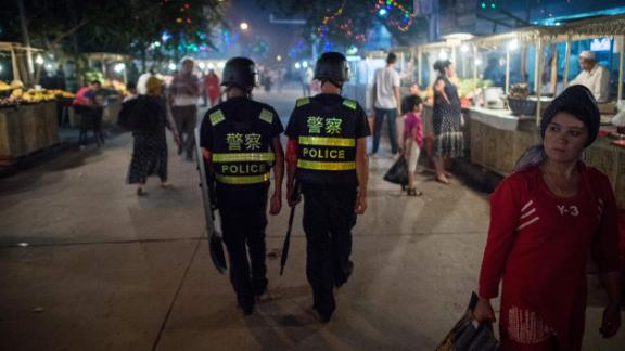 This picture taken on June 25, 2017 shows police patrolling in a night food market near the Id Kah Mosque in Kashgar in China