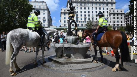 Police officers water their horses at a fountain in London's Green Park.