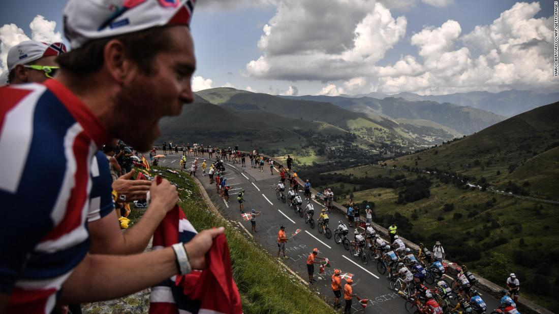 Spectators cheer as a pack of cyclists rides uphill during the 17th stage of the Tour de France on Wednesday, July 25.
