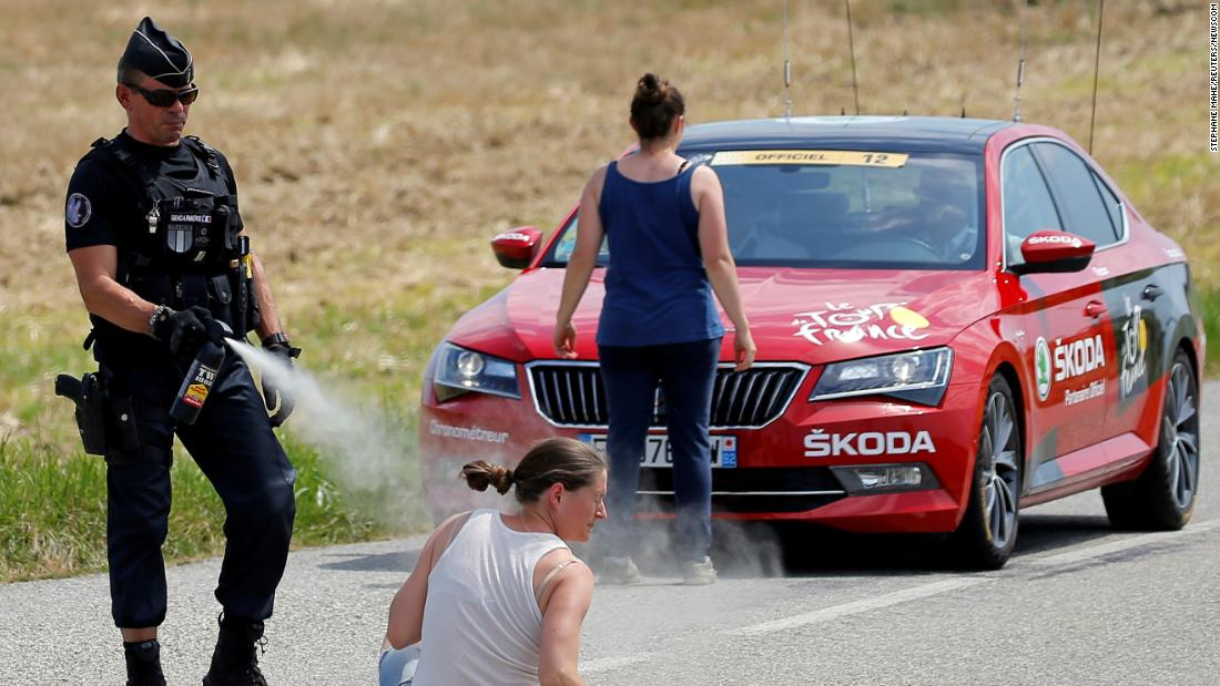 "A police officer sprays tear gas at one protester as another protester stands in front of the race director's car on July 24. Protesting farmers had blocked the road with hay bales, and <a href=""https://www.cnn.com/2018/07/24/sport/tour-de-france-protesters-pepper-spray/index.html"" target=""_blank"">the race was temporarily halted</a> after tear gas inadvertently got into the eyes of some riders."