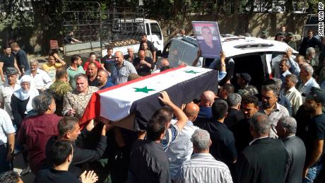 Mourners carry a coffin of one of the victims of Wednesday's attack, in a photo released by SANA.
