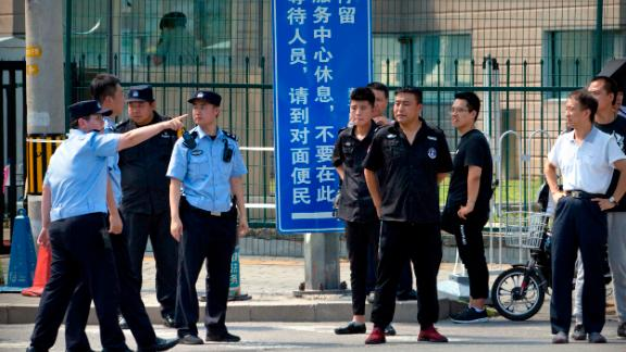 Chinese security personnel stand outside the U.S. Embassy, in the background, after a reported blast occurred nearby in Beijing, Thursday, July 26, 2018. (AP Photo/Mark Schiefelbein)