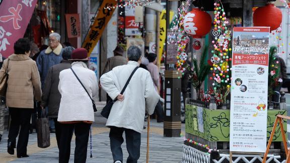 Elderly people walk in the street at Kouganji Temple in Tokyo.