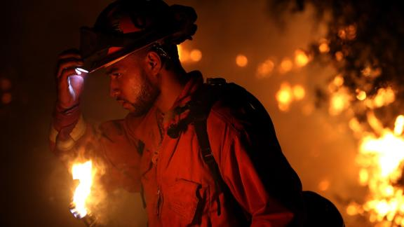 A firefighter monitors a backfire while battling the larger Carr Fire on Friday in Redding.