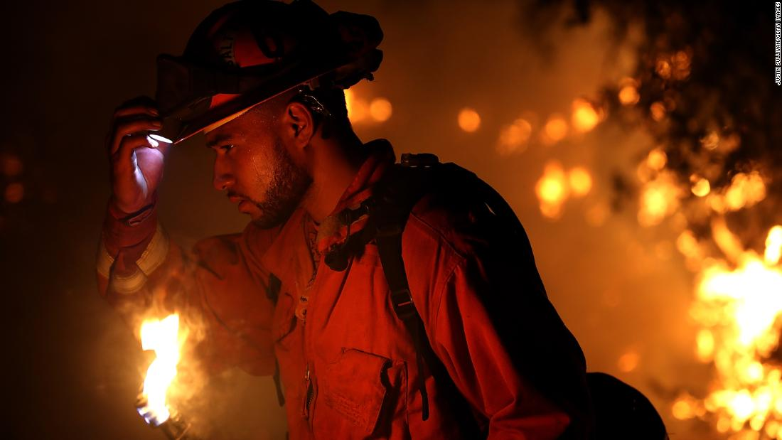 A firefighter monitors a backfire while battling the Carr Fire on July 27. The fire grew rapidly Thursday night, ravaging several small communities and jumping the Sacramento River before threatening the outskirts of Redding.