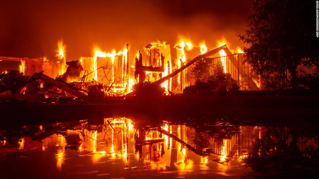 A burning home is reflected by a pool in Redding, California, on Friday, July 27. The Carr Fire is one of six large wildfires that California has been fighting.