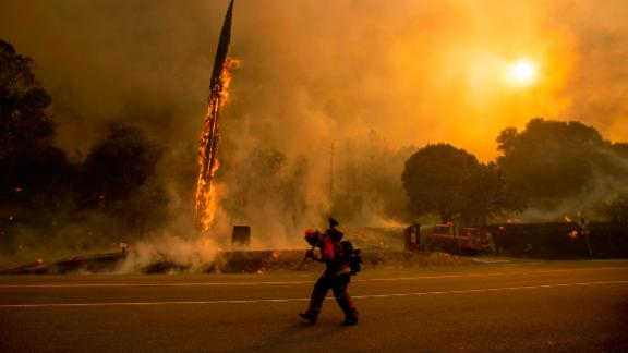 A firefighter walks along Highway 299 as the Carr Fire tears through Shasta on July 26.