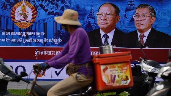 A cyclist rides past an electoral hoarding of Cambodia