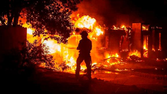 A firefighter battles the fast-moving Carr Fire on Thursday at a house in Redding, California.